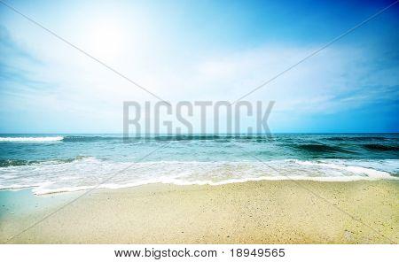 Clean beach under blue sky