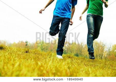 Carefree friends running together on green meadow