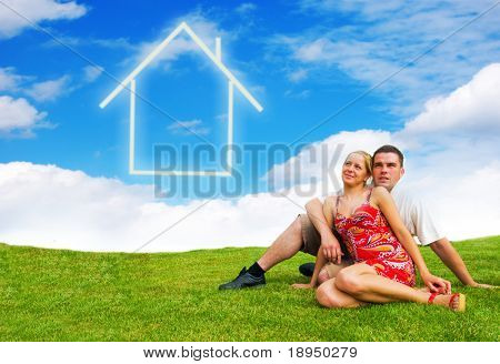 Happy young couple looking at the sky dreaming about their future house