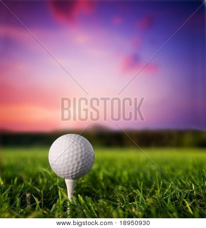 Bola de golfe no tee. Grama verde, pôr do sol.