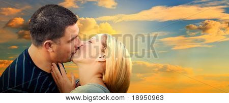 Couple kissing in romantic love scenery on sunset sky. Panorama version