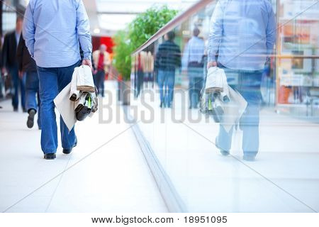 People in rush in a modern shopping mall. Close up and reflection of a man walking