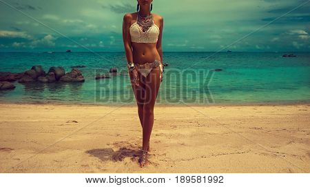 poster of Slim and tanned girl in trendy Boho style on the beach. Girl in a white knit swimsuit with silver jewelry . Bracelets and rings with turquoise stones.