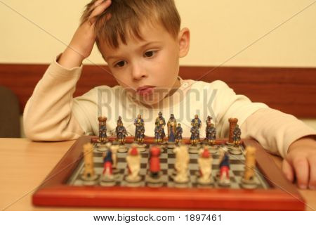 The Boy Plays A Chess Behind A Table