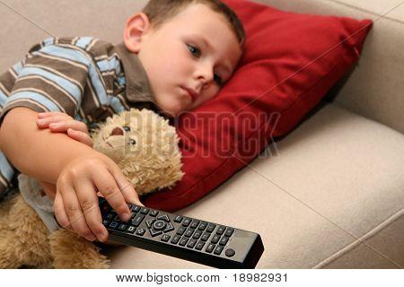 Boy watching TV with sweet teddy bear