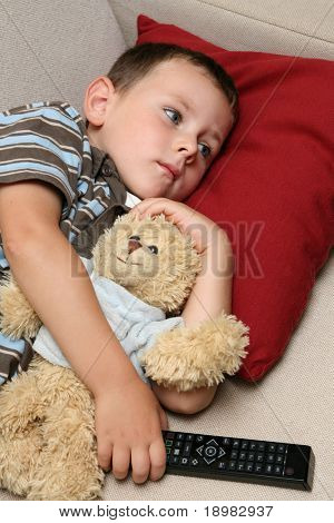 Boy watching TV with sweet teddy bear