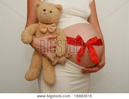 Pregnant belly with red ribbon and sweet teddy bear. Nine month. Third trimester.
