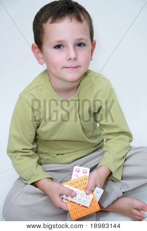 Child holding medicine. Five years old boy holding pills in hands.