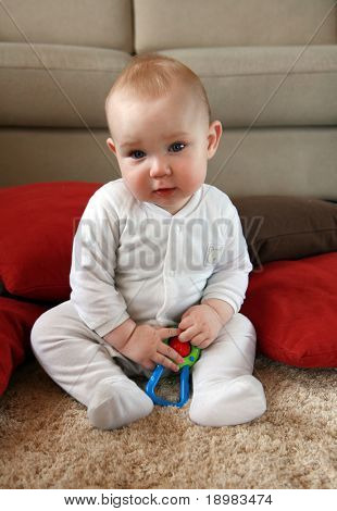 Baby boy with his first toys. Portrait of six months old sweet baby.