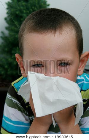 Five years old boy with tissue blowing his nose. Child with allergy, conjunctivitis and black rings round his eyes.