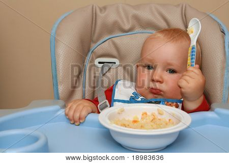 10 months old sad baby boy practice eating. Baby with a spoon.