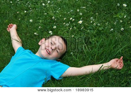 5 years old child lying on the grass.