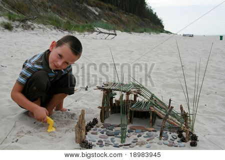 Happy summer child. Kid playing on the beach.5 years old boy building a sandcastle.
