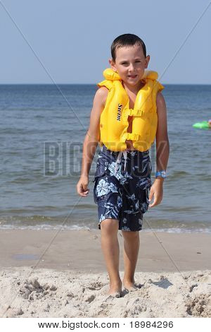 Six  years old  boy wearing in life jacket and learning to swim in the sea.
