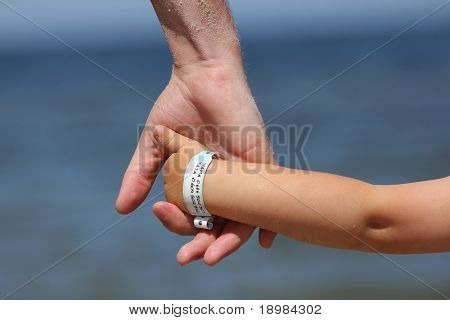 Baby with info band on his wrist with name and his mother's and father's  phone number.