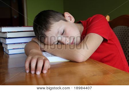 8 years old boy doing his boring homework and sleeping