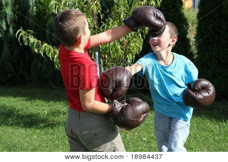 Child fighting with boxing gloves. Sibling, two boys boxing.