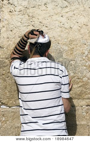 The young jewish men praying at a western wall