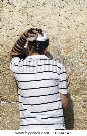 The young jewish men praying at a western wall