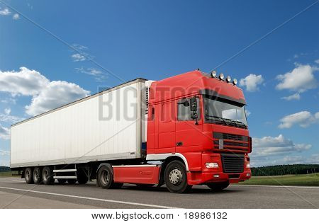 Single red lorry with white trailer over blue sky on the road.