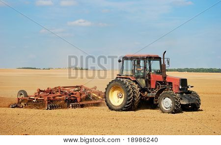 Ploughing tractor in yellow field outdoors in summer with plough
