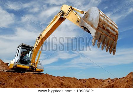 Excavator standing in sandpit with raised bucket over cloudscape sky