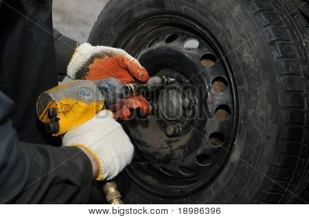 two hands making tyre fitting with air compressed wrench (screwing up bolts)