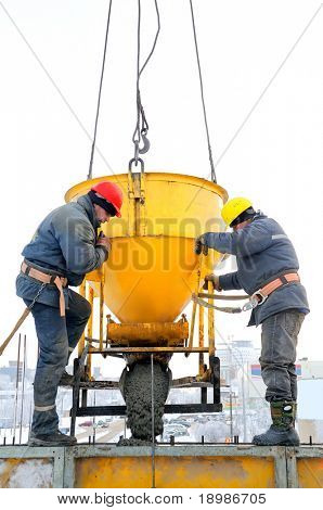 Two construction building workers at construction site pouring concrete in mould