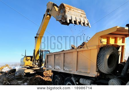 Loader Excavator loading body of a dump truck tipper at open cast over blue sky in winter