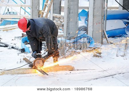 worker in workwear cutting metal reinforcing bar with abrasive cutoff saw disk