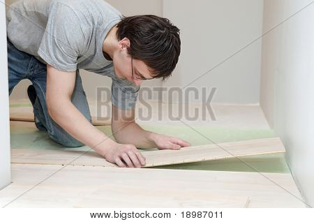 Young worker carpenter laying a floor with laminated flooring boards