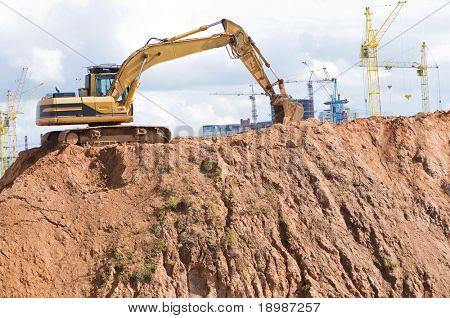 loader excavator in open sand mine over construction site