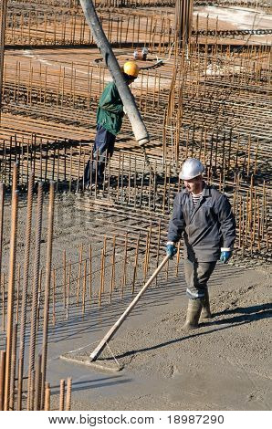 two builder workers during concrete works at construction site. Levelling and pouring