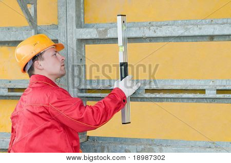 builder worker checking vertical with digital level tool at construction site
