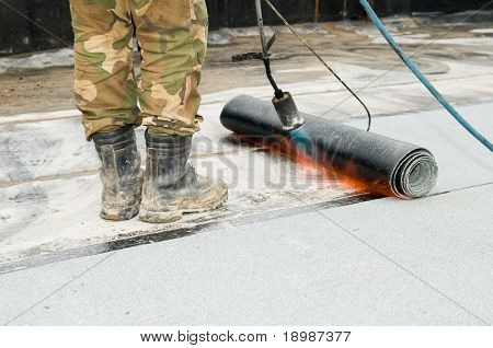close-up process of roofing felt roll and torch blowpipes with open flame