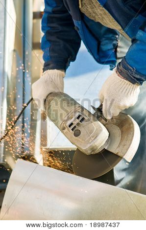Close-up works with circular abrasive cutoff saw grinding machine and sparkles