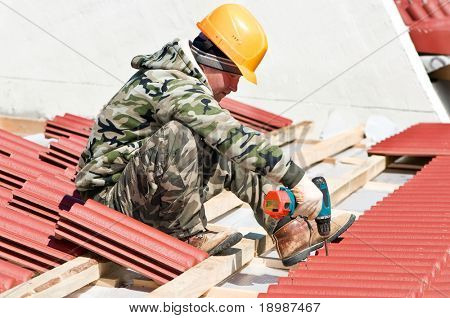 builder roofer working with screwdriver at roofing construction works