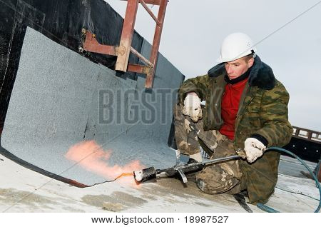 Roofing asphalt bitumen felt installation with heating and melting roll by torch on flame