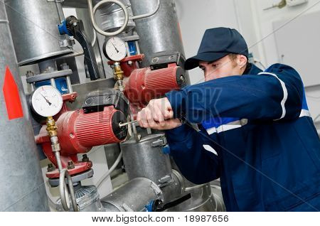 Instandhalter, die Überprüfung der technischer Daten von Heizanlagen System in einem Heizraum