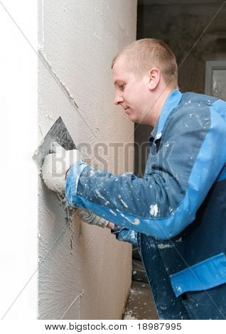 Plasterer at indoor renovation decoration with putty knife
