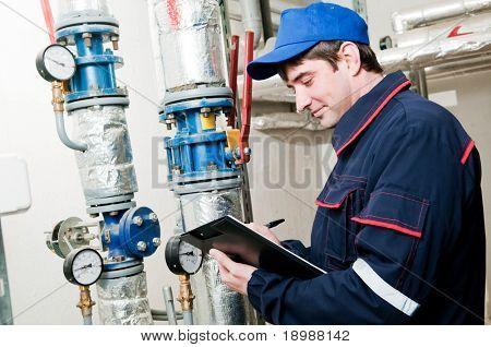 Ingeniero de mantenimiento, comprobación de datos técnicos del equipo de sistema en un cuarto de caldera de calefacción