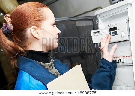 woman engineer checking technical data of heating system equipment in a boiler room