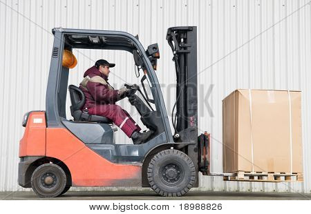 warehouse forklift loader with cardboard freight moving on a ramp