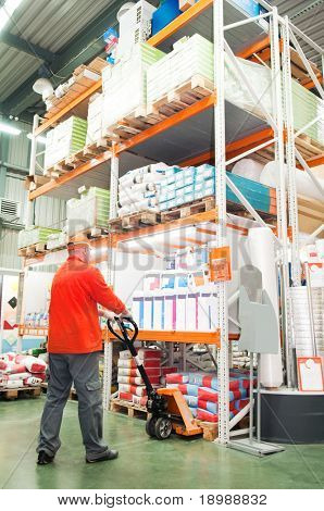 worker distributing goods in a warehouse with forklift truck loader