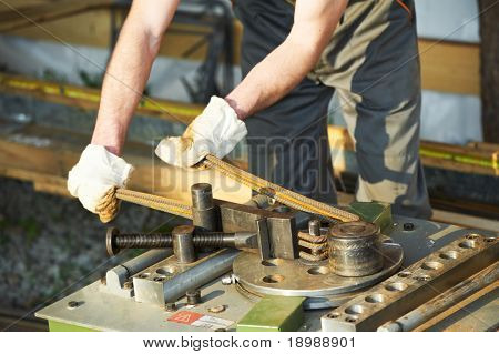 close-up worker hands in protective gloves bending concrete reinforcing metal rods by bender equipment