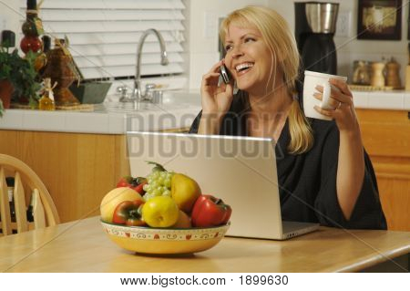 Woman Smiling, In Her Kitchen On Cell Phone Sitting In Front Of Laptop.