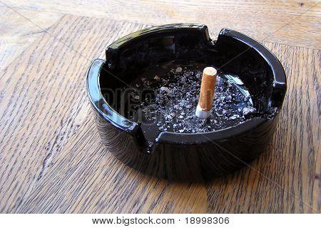 Fertige Zigarette in schwarz Aschenbecher mit etwas Asche.