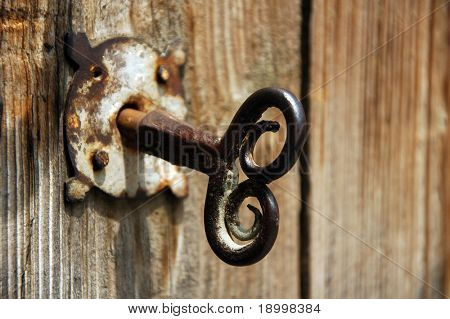 Old house key in wooden doors.