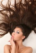 pic of brown-haired  - attractive young adult lying on white background with flowing hair - JPG
