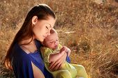 stock photo of baby-boy  - young mother and newborn baby sitting on grass - JPG